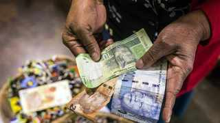 File image :A ten rand, twenty rand and a hundred rand note held in a person's hands, being counted. IOL.
