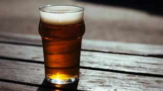 File image: A glass of beer on a wooden table. IOL.