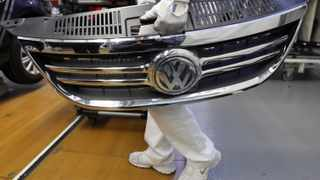 An employee holds a part for the bodywork of a Volkswagen Tiguan at the Volkswagen headquarters in Wolfsburg. The car manufacturer is in talks with Algeria about a possible venture in the North African country.