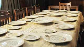 "Roela Hattingh's installation When the Gods Come to Eat invites the ""reader"" to take a seat and read the story on the plates. From the collection Transgressions and Boundaries of the Page, North-West University."