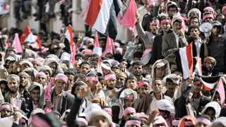 Yemeni demonstrators hold their national flags during a rally calling for an end to the government of President Ali Abdullah Saleh, in the capital Sanaa yesterday. Photo: AP.