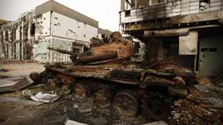 A destroyed tank belonging to forces loyal to Libyan leader Muammar Gaddafi is seen near a damaged hospital building in the west Libyan city of Misrata.