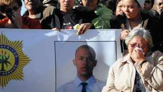 Christine Cloete, 69, flanked by family, sits next to a banner of her murdered grandson, Cannon Cloete, during a peace march in Wallacedene in Kraaifontein. Photo: Neil Baynes