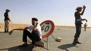 Anti-Gaddafi fighters man a checkpoint in the north of the besieged city of Bani Walid.