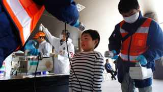 A boy is screened for radiation contamination before entering an evacuation center in Fukushima, Japan. The March 11, 2011 earthquake and tsunami caused massive death and destruction across northeastern Japan. But those who live near the crippled Fukushima Dai-ichi nuclear plant face a burden atop the losses they've already suffered: a fear of radiation that experts say could prove more unhealthy in the long run than the still-low levels of leaked radiation itself.