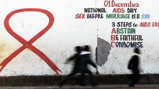 Children run past an Aids ribbon mural at a school in Khutsong, west of Joburg. UNAids says the Aids pandemic is in decline, but countries need to invest smartly to achieve substantial progress in fighting it.