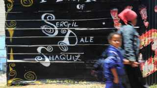 Cape Town.  111129. Johanna Samuels, clutching the hand of five-year-old Ashleen Peters(cor), walks by a mural in Lavender Hill dedicated to three teenagers gunned down earlier this year.  Photo by Michael Walker