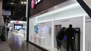 Workers arrange a display of home appliances at an LG Electronics booth prepare for the 2012 International CES at the Las Vegas Convention Centre.