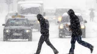 Men cross a street during a snowfall in Macedonia's capital Skopje, Monday, Feb. 13, 2012. Since the end of January, Eastern Europe has been pummeled by a record-breaking cold snap and the heaviest snowfall in recent memory. (AP Photo/Boris Grdanoski)