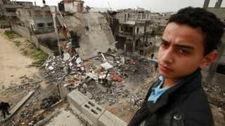 A Palestinian youth stands near a destroyed building after an Israeli air strike in Jabalya in the northern Gaza Strip on Monday.