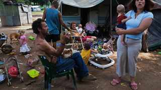Andre Coetzee, 57, (L) sits with a neighbouring family at a squatter camp for poor white South Africans at Coronation Park in Krugersdorp, March 13, 2010. A shift in racial hiring practices and the recent global economic crisis means many white South Africans have fallen on hard times. Researchers now estimate some 450 000 whites, of a total white population of 4.5-million,  live below the poverty line and 100,000 are struggling just to survive in places such Coronation Park, a former caravan camp currently home to more than 400 white squatters. Picture taken March 13, 2010. To match feature SAFRICA-WHITES    REUTERS/Finbarr O'Reilly  (SOUTH AFRICA)