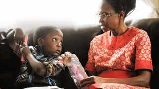 From left to right 6 year old Tshego Kakulubela a month after his cochlear implants handing over his mother's day gift to his mother Sinah Kakulubela.  Picture: Mujahid Safodien 13 05 2012