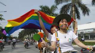 Participants carry a rainbow flag while attending Vietnam's first-ever gay pride parade in Hanoi.