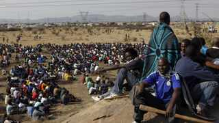 FILE PHOTO: Striking miners gather outside a South African mine in Rustenburg.