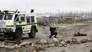 A police officer fires shots to disperse miners at Lonmin's Marikana mine on September 15. File photo
