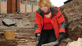 File photo: Karen Ladniuk, from the Richard III society, cleaning a path made from re-used medieval tiles during an excavation of the car park behind council offices in Leicester.