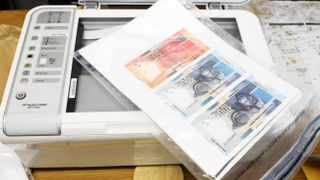 Cape Town -05-12-2012  Delft Police inspect the fake money and the printer they confirscated at a house in Auber Street Delft South pix Pix Patrick Louw story Megan