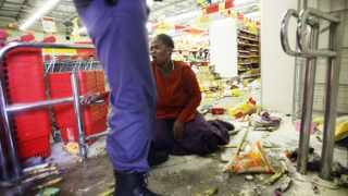 Cape Town - 130109 - Farm protests erupted in Grabouw as looters pillaged Shoprite. Later, police raided the Rooi Dakke shacks where looters were trying to break into a spaza shop there. 22 year old Ibrahim Abdule, standing guard outside his damaged shop, axe in hand, was injured on the hand as the attackers, armed with sticks and knives tried to break into his shop, something that has happened numerously before. Police used rubber bullets and flashbangs to clear the protesters. One person was arrested as she tried to flee the cops, but was apprehended before she made it out of the store - Shoprite. PICTURE: THOMAS HOLDER