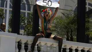 An activist of the Kiev based feminist protest group Femen holds a sign during a protest inside the famous Copacabana palace hotel in Rio de Janeiro.