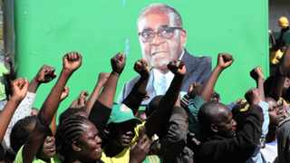 Supporters welcome President Robert Mugabe, seen on a poster at rear, during a campaign rally in Chitungiwiza recently. Zimbabwe is to hold presidential elections on Wednesday. Picture: Tsvangirayi Mukwazhi