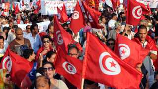 Tunisians wave their national flag as they march outside the National Assembly in Tunis on September 7, 2013, to mark the 40th day since the assassination of opposition politician Mohamed Brahmi.