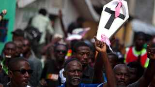 A demonstrator holds up a mock coffin representing the nation's problems during a march against President Michel Martelly's government in Port-au-Prince, Haiti.