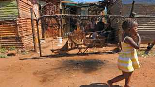 A child walks past the scortched markings on the spot where traditional healer Magagula was burnt to death by an angry mob, in Chris Hani neighbourhood/section of Khutsong Mob Justice erupts in Khutsong. Picture: Antoine de Ras, 04/11/2013