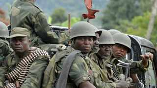 Democratic Republic of Congo FARDC army soldiers sit at the back of a pick-up truck as they head towards the Mbuzi hilltop, near Rutshuru, on November 4, 2013.