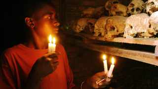 FILE -Apollan Odetta, a survivor from the 1994 Rwandan Genocide light candles at a mass grave in Nyamata, Rwanda. Two decades after the Rwandan genocide, France is finally opening what critics called its blind eye to justice over the killings. (AP Photo/Sayyid Azim, File)