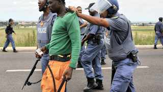 04/02/2014 SAPS members arrest a protesting Zithobeni resident minutes after they dispursed them with rubber bullets during their service delivery protest. Residents are demanding they be allowed to hand over a memorandum to Tshwane Mayor Kgosientso Ramokgopa. Picture: Phill Magakoe