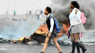 06/02/2014 School children walk past burning tyres moments afetr angry Hebron residents took to the streets demanding better service delivery from government. Picture: Phill Magakoe