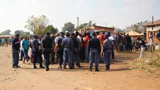 156 05.07.2014 Police Officers command residents of Everest in Springs to move away from the polling station if they are not voting. Community members gathered metres away from the station to say that they wont vote. Picture:Sharon Seretlo 078 005 4945