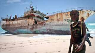 File picture - A masked pirate stands near a ship which was beached after the ransom was paid for it. AP Photo/Farah Abdi Warsameh