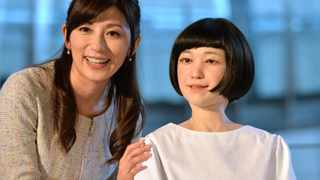 Japanese announcer Aki Nakata poses with a new humanoid robot named 'Kodomoroid' at the National Museum of Emerging Science and Technology in Tokyo.