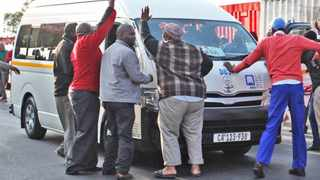 Feebearing - Cape Town - 140915 - Taxi drivers went on strike at the Nyanga Taxi Rank because they are unhappy with the fines they have to pay and also fees connected to impounded vehicles. Pictured: Taxi drivers stop a taxi in the rank and remove the occupants to prevent them from leaving.  REPORTER: NATASHA BEZUIDENHOUDT. PICTURE: WILLEM LAW.