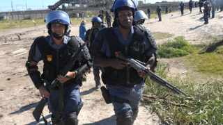 Cape Town 150407.  Police officers  remove people that invaded a piece of Land near Nolungise station in Khayelitsha.Picture Cindy Waxa.Reporter Kieran/Argus