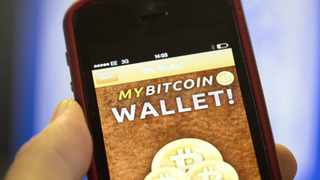 An Apple Inc. iPhone5 displays the Bitcoin Wallet smartphone app in this arranged photograph at the Pembury Tavern in London, U.K., on Wednesday, Oct. 9, 2013. Bitcoins are being adopted by a few merchants, enabling customers to buy beer at Pembury Tavern in East London, cocktails at EVR bar in New York and dessert at Cups and Cakes Bakery in San Francisco. Photographer: Simon Dawson/Bloomberg