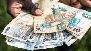 A man holds a collection of Zambian kwacha banknotes in this arranged photograph in Lusaka, Zambia, on Thursday, Oct. 8, 2015. Zambian Finance Minister Alexander Chikwanda is seeking to restore confidence in the economy to help reverse the world's worst currency performance, record borrowing costs and sliding growth. Photographer: Waldo Swiegers/Bloomberg