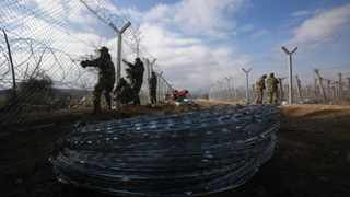 Macedonian army soldiers erect a second fence on the border line with Greece, near the southern Macedonia's town of Gevgelija. Picture: AP Photo/Boris Grdanoski