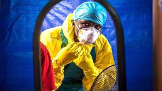 A healthcare worker dons protective gear before entering an Ebola treatment centre. Picture: AP Photo/Michael Duff, File