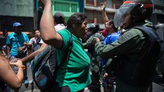 A woman confronts a National Guard soldier during a protest demanding food, a few blocks from Miraflores presidential palace in Caracas. Picture: AP Photo/Ariana Cubillos