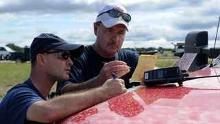 Fort Hood firefighters William Smith and Capt. Donald Donahoo mark map coordinates during search and recovery efforts for four missing Soldiers after a swift water accident the day prior at Fort Hood, Texas.