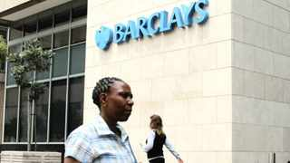 Pedestrians pass a logo outside the offices of Barclays Plc in Johannesburg, South Africa, on Thursday, Dec. 12, 2013. Inflation in Africa's biggest economy slowed for a third month in November, staying within the Reserve Bank's 3 percent to 6 percent target range and relieving pressure on Governor Gill Marcus to start raising interest rates early next year. Photographer: Dean Hutton/Bloomberg