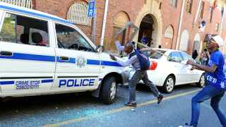 Protesting students smashed a police car as they ran from Parliament after handing in their memorandum. Photo: Phando Jikelo