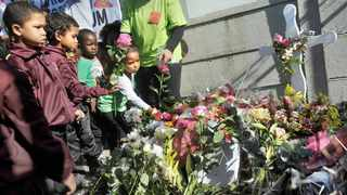 TRAUMATIC MOMENT: Children place flowers at the site where the body of Courtney Pieters was found in a shallow grave in May last year. She was raped and murdered. Community Safety MEC Dan Plato, children and communitymembers from Eerste River visited the crime scene. Picture: Armand Hough/African News Agency(ANA)