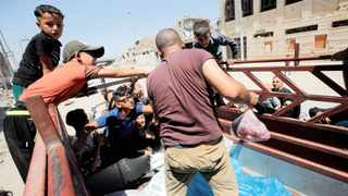 Residents gather around a car that distributes meat to the poor in the old city of Mosul, Iraq, this week. Picture : Khalid Al-Mousily/Reuters