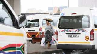 A woman makes her way to a taxi in Durban's central business district. With yesterday's fuel price increase, consumers are feeling the pinch of the rising costs of transport and food.