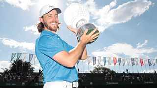 Tommy Fleetwood is all smiles after lifting the Nedbank Golf Challenge trophy at Sun City yesterday. Photo: Michael Vlismas