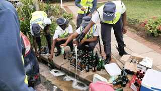 Metro police officers pour confiscated liquor down the drain.