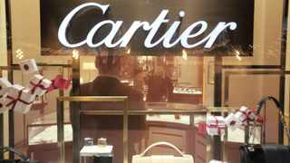 Customers browse luxury products for sale inside a Cartier store. Richemont plans to introduce a model that has not been seen in listed companies with the departure of its chief executive. File Photo: Bloomberg